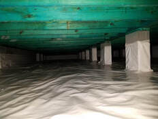 Dark crawl space encapsulated with 20 mil vapor barrier in Birmingham, Alabama